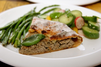A slice of Open Face Lamb Pie with asparagus and cucumber salad