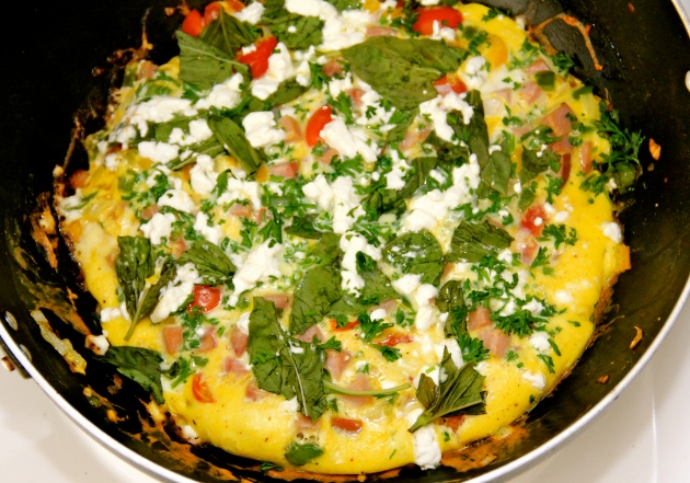 Ham omelette with vegetables, feta and fresh herbs