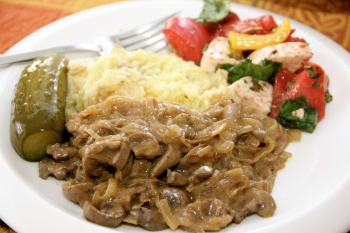 Veal Kidney Stroganoff served with mashed potatoes, pickle, and basic tomato salad
