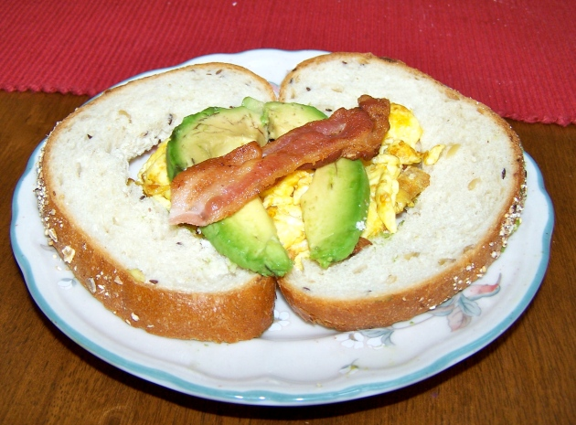 A Valentine's Day breakfast -- a heart shaped toast stuffed with eggs and avocado, with bacon for an arrow