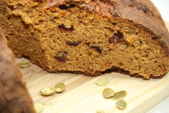 A close up of a roasted pumpkin sourdough with cranberries and pumpkin seed