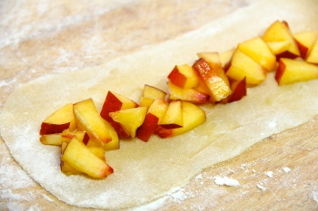 Arranging the chopped nectarines on a strip of dough