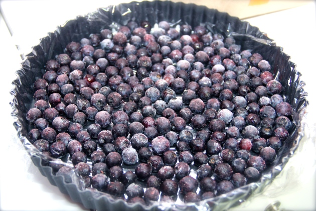 Frozen blueberries arrange on a bottom of a tart pan