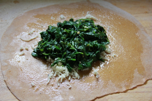 Filling the plăcintă pie with cheese and spinach