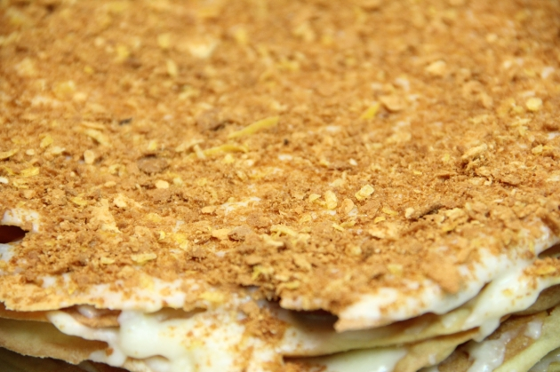 Making Russian Napoleon: topping the cake with finely crumbled crust